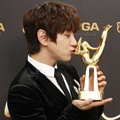 Hwang Chi Yeul mencium trofi Disc Bonsang miliknya di Golden Disc Awards 2018.